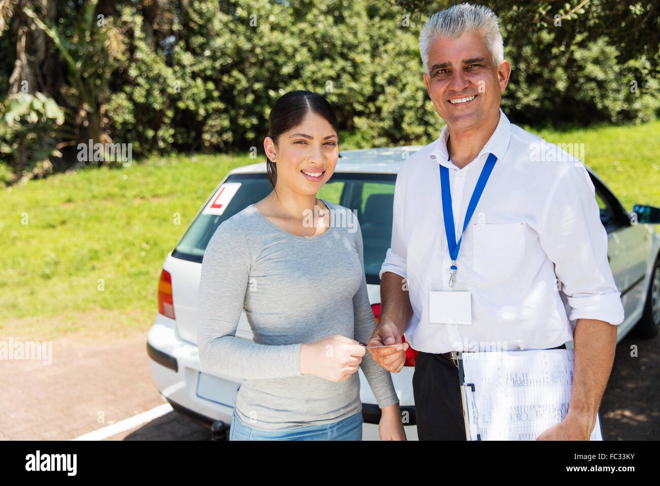 portrait of driving instructor handing driving license to student driver Stock Photo