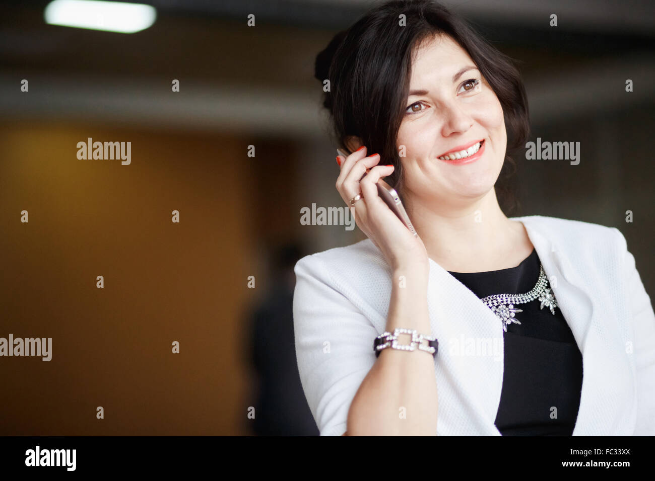 Attractive business woman talking on the phone, beaming smile, positive image, dressed white suit with strict black - Stock Image