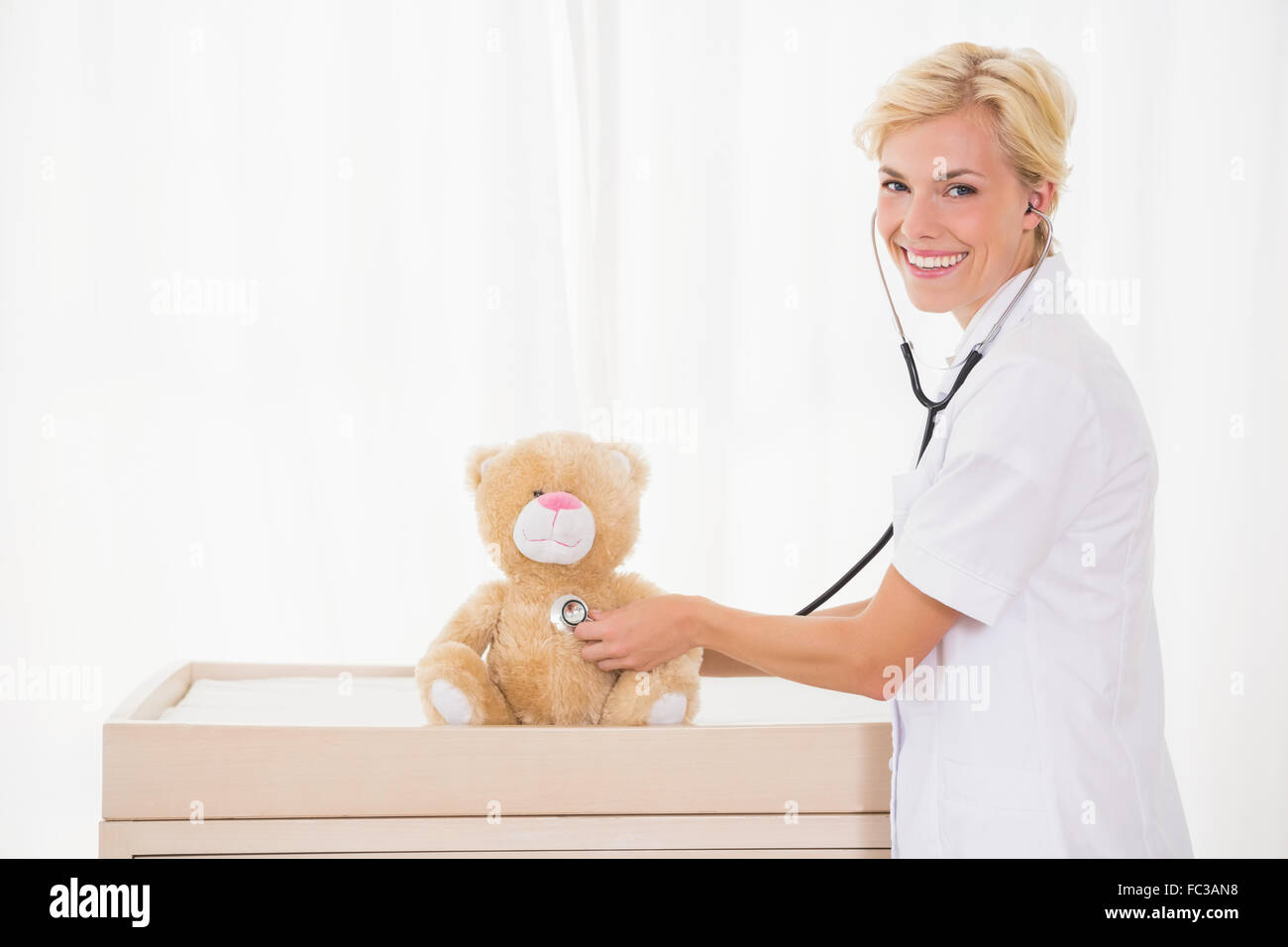 Smiling blonde doctor with stethoscope in the teddy bear - Stock Image