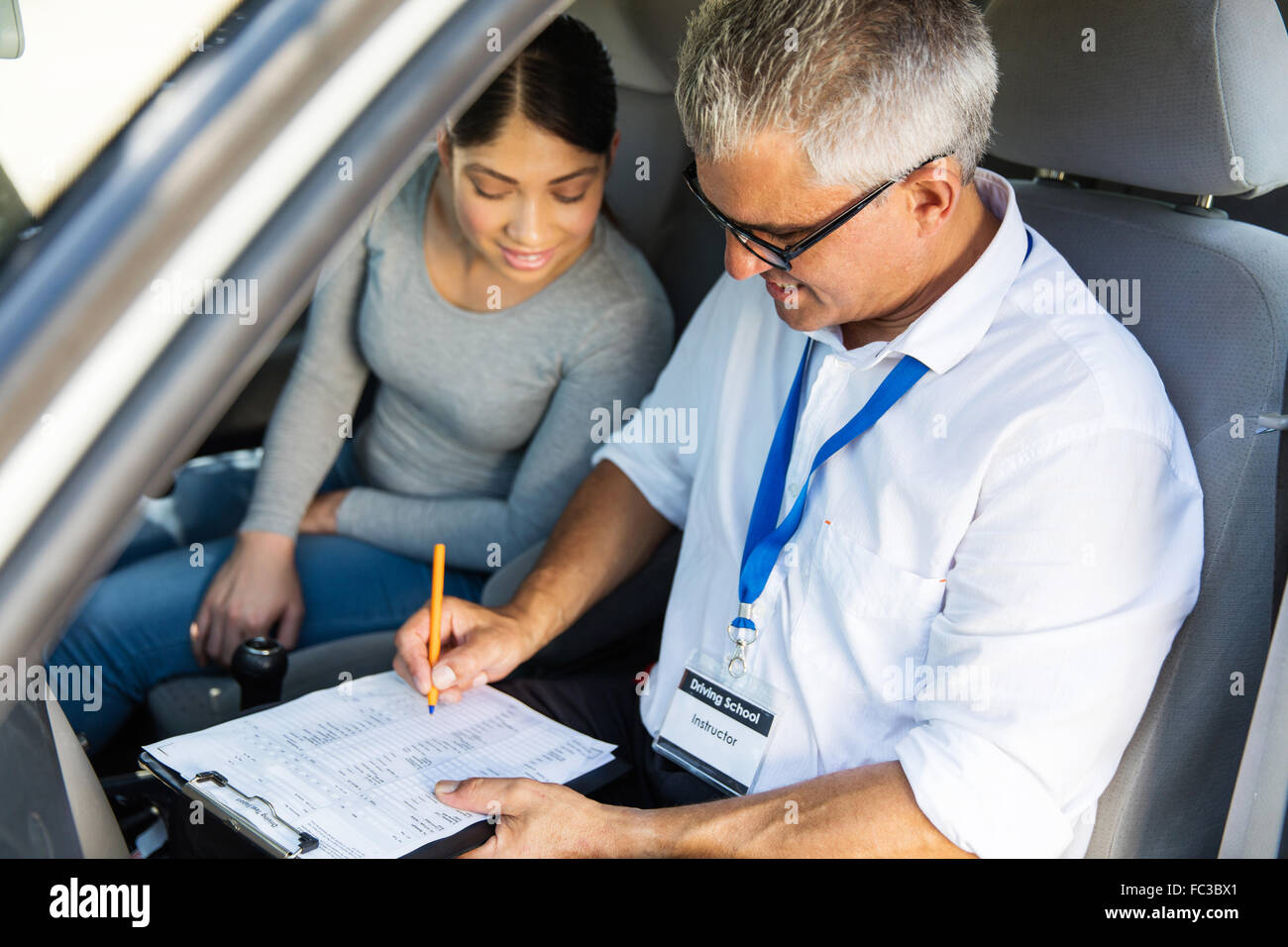 portrait of senior driving instructor and student driver during lesson - Stock Image