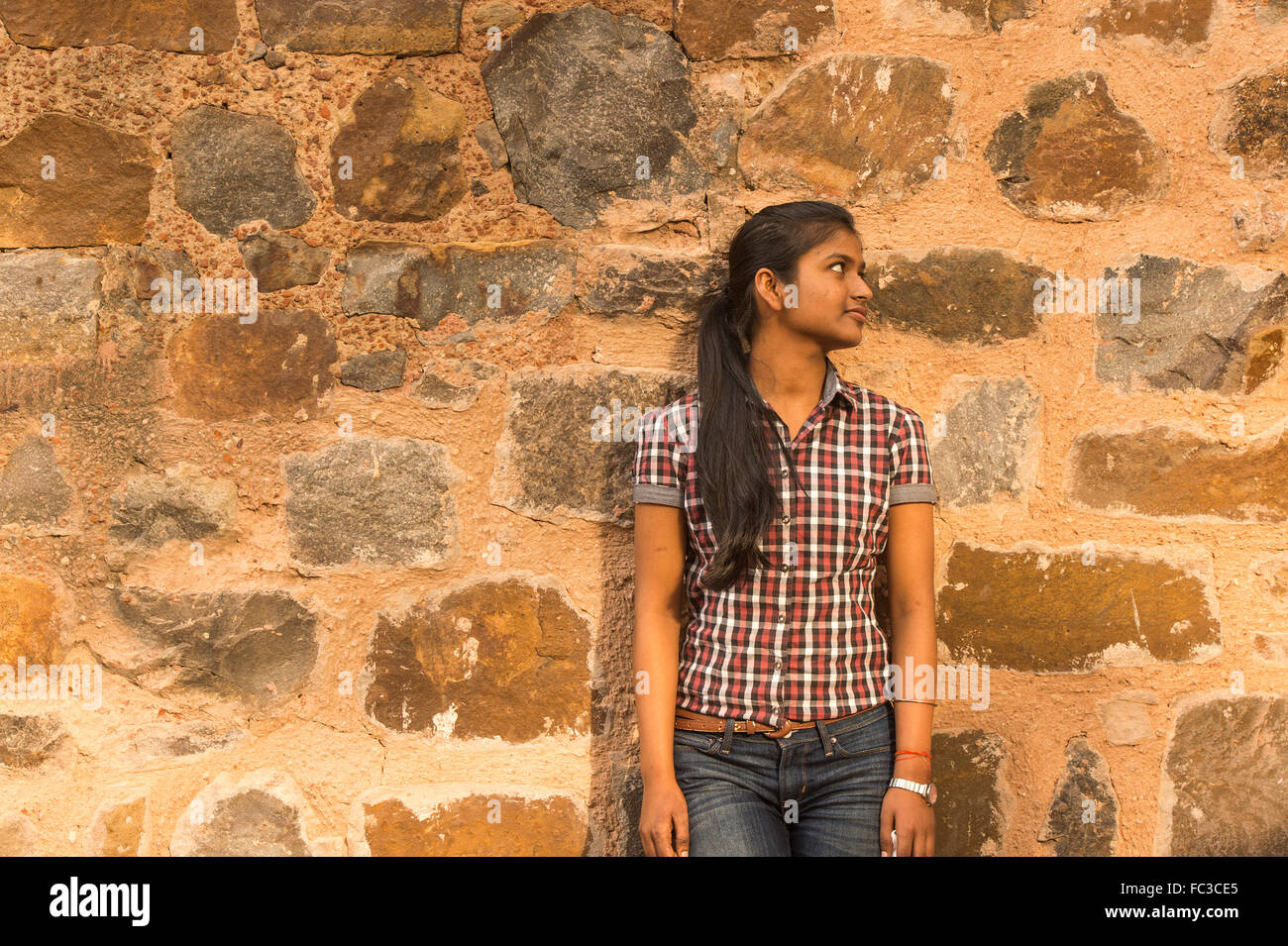 A local women standint at the wall of Ancient underground step-well (Ugrasen ki Baoli) in Delhi. India. - Stock Image