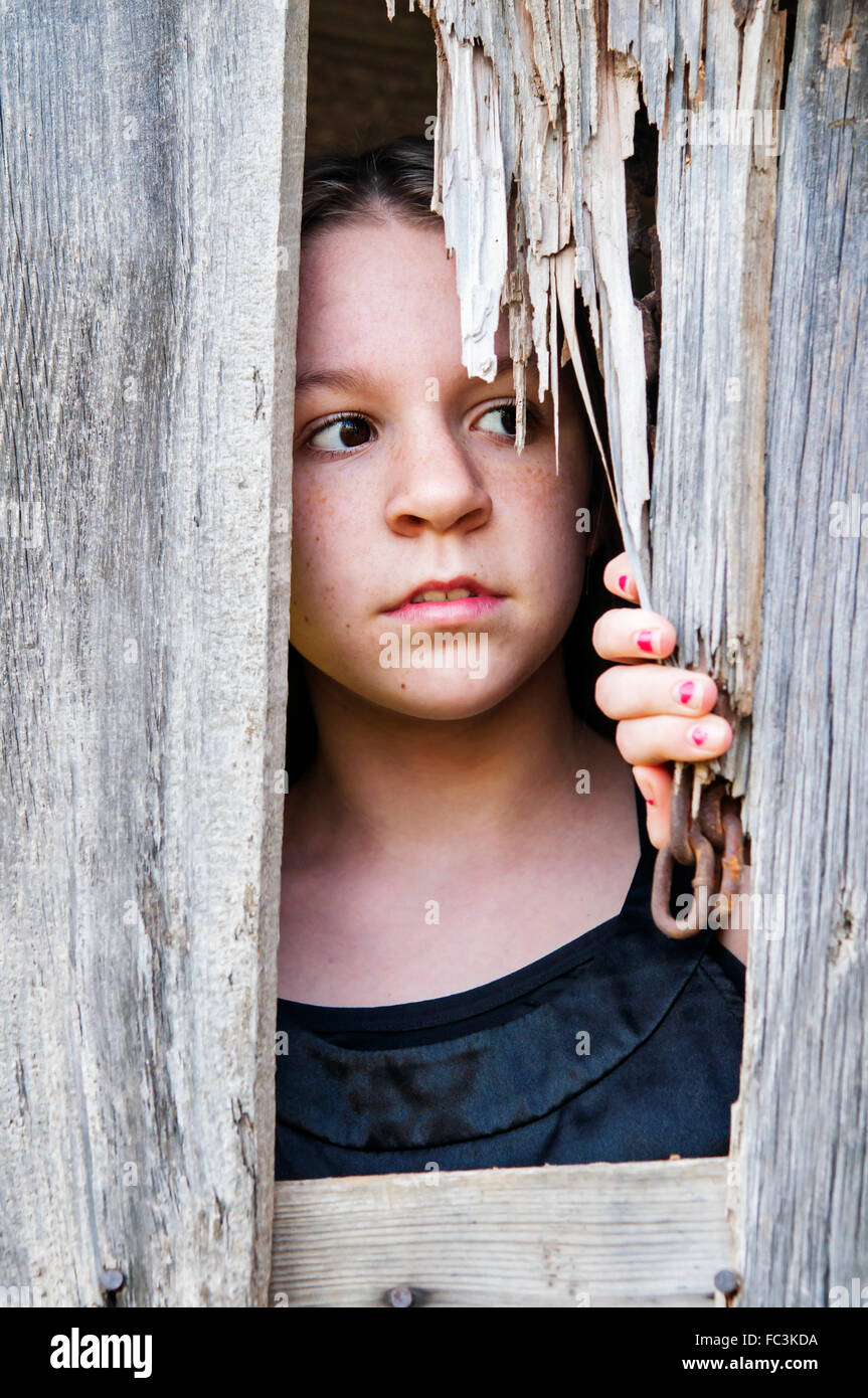 Girl looking out of barn - Stock Image