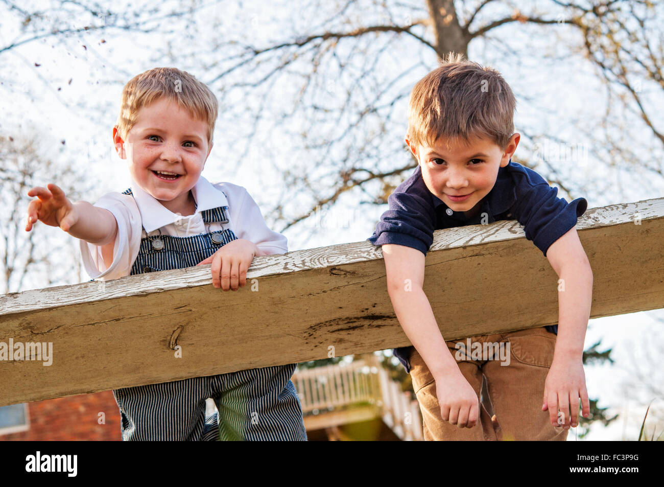 Two boys swinging on bellies - Stock Image