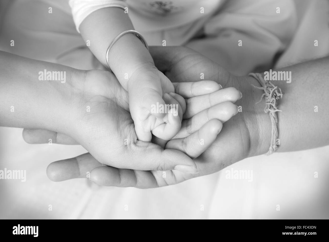 Baby's hand upon her parent hand - Stock Image