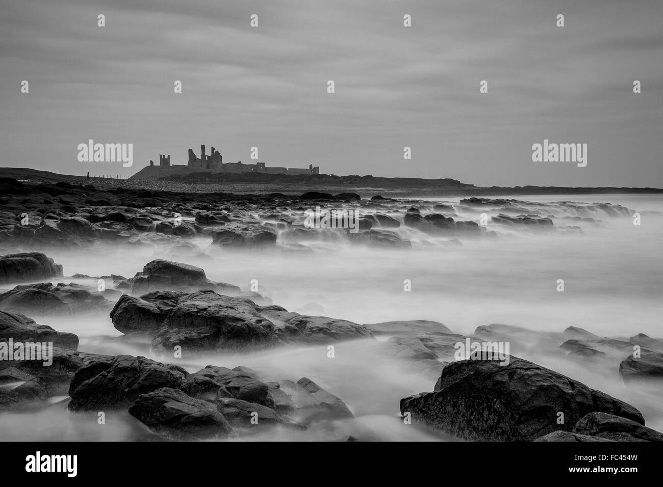 Monochrome long exposure capture of Dunstanburgh Castle Northumberland - Stock Image