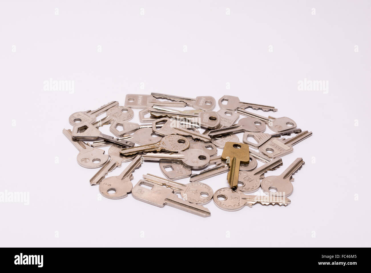 Old keys arranged on a while background - Stock Image