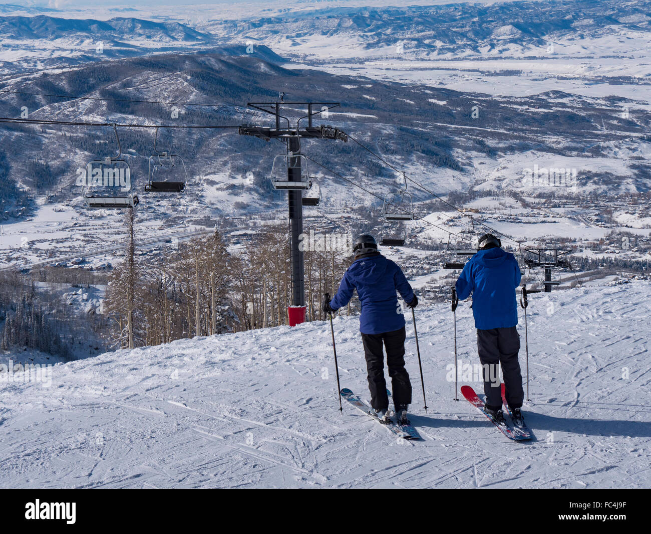 Skiers begin their descent from behind the Four Points Lodge, Steamboat Ski Resort, Steamboat Springs, Colorado. - Stock Image