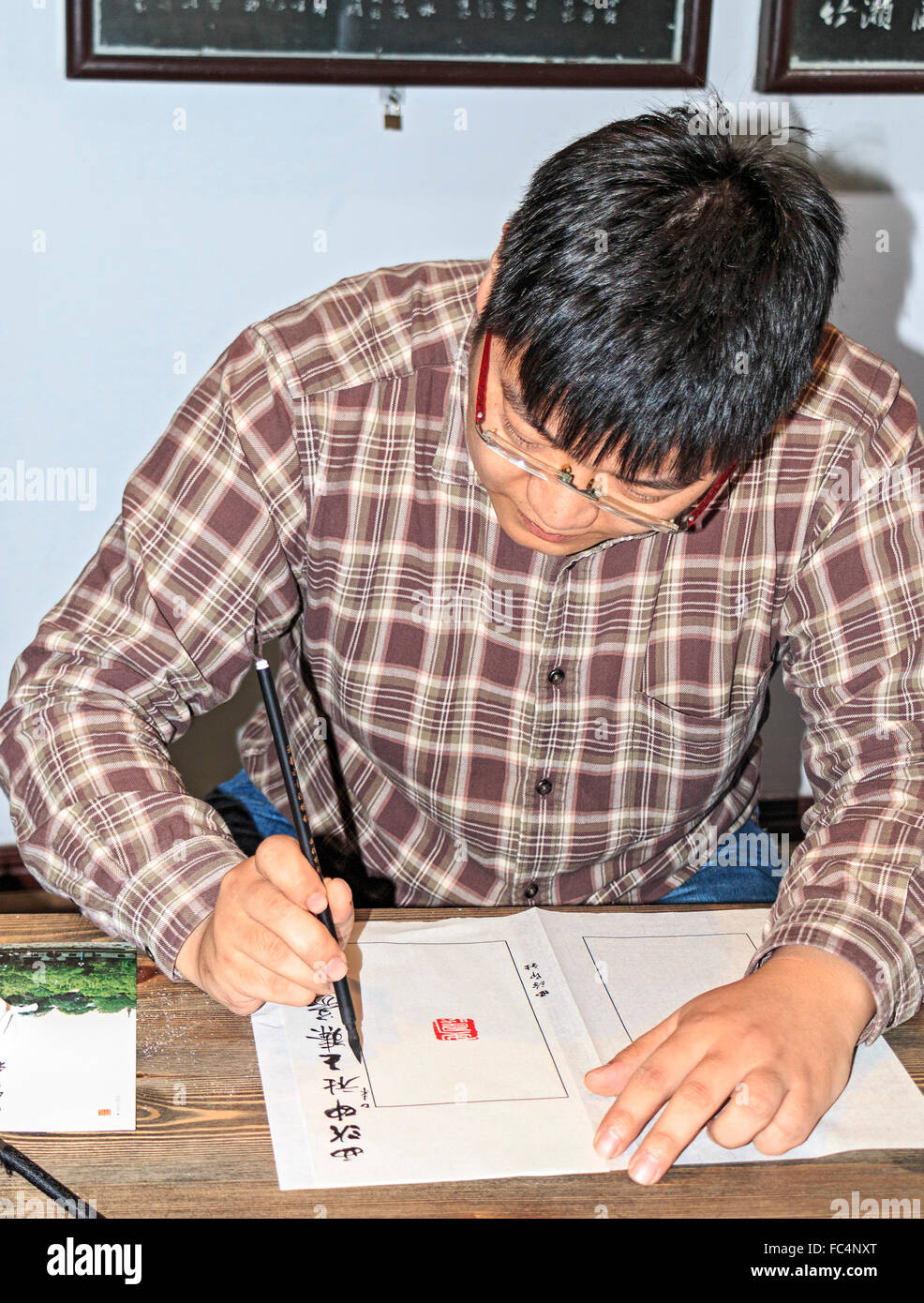 Wang Zhen, a master engraver, shows students how to carve a seal or chop at Xiling Seal Engraver's society in - Stock Image