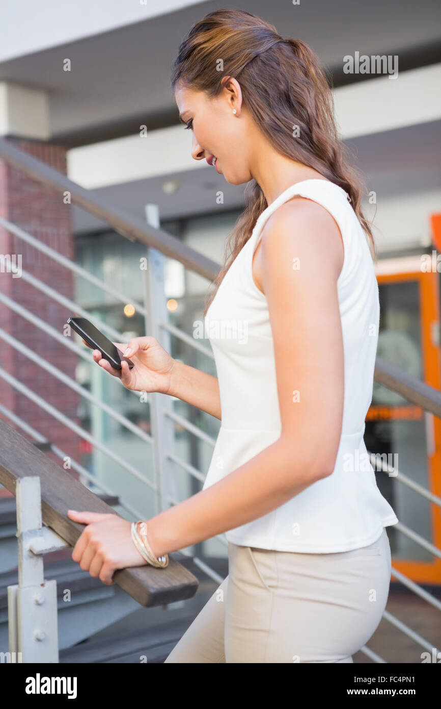 Smiling woman going upstairs while using her smartphone Stock Photo