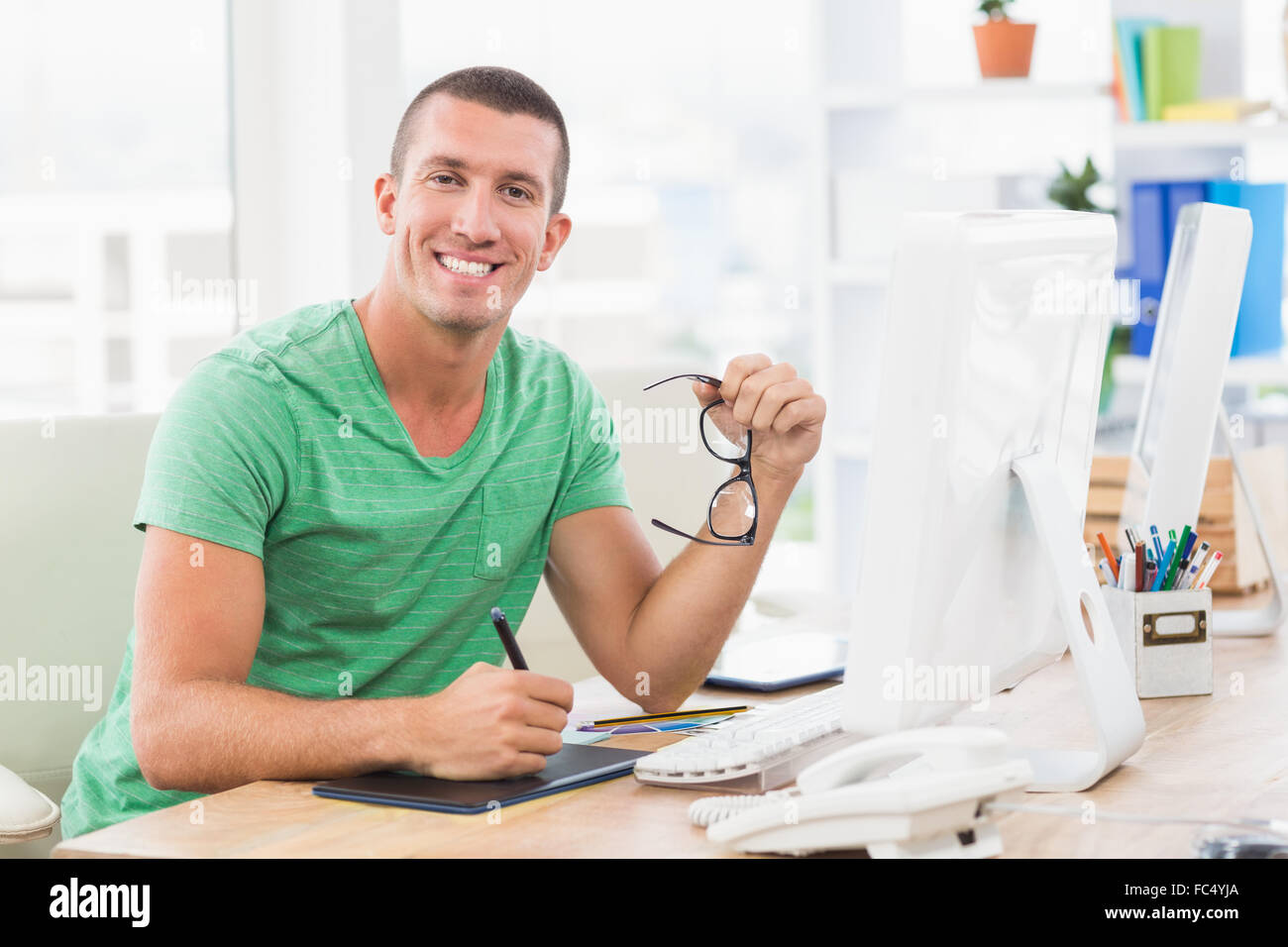 Young creative businessman drawing on graphic tablet - Stock Image