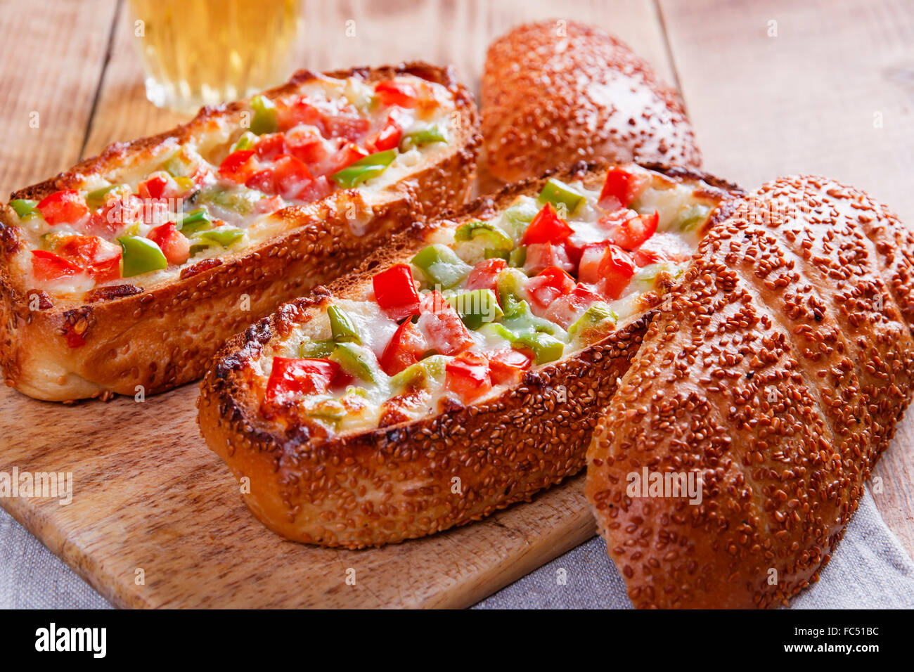 baked baguette stuffed with vegetables and cheese - Stock Image