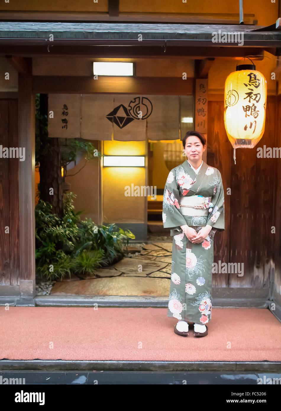 A Japanese lady stands at the entrance door of a Japanese hotel to welcome guests. - Stock Image