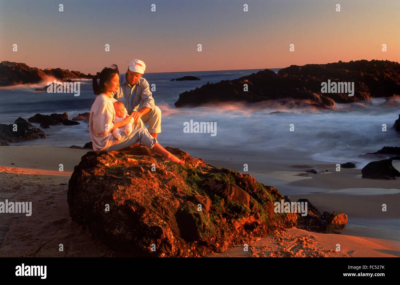 Family of three at sunset in Laguna Beach California USA Stock Photo