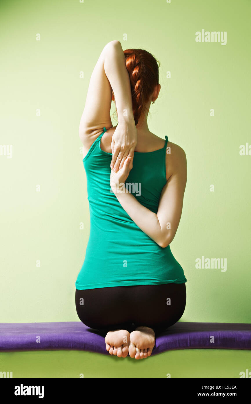Yoga woman clutches hands behind back - Stock Image