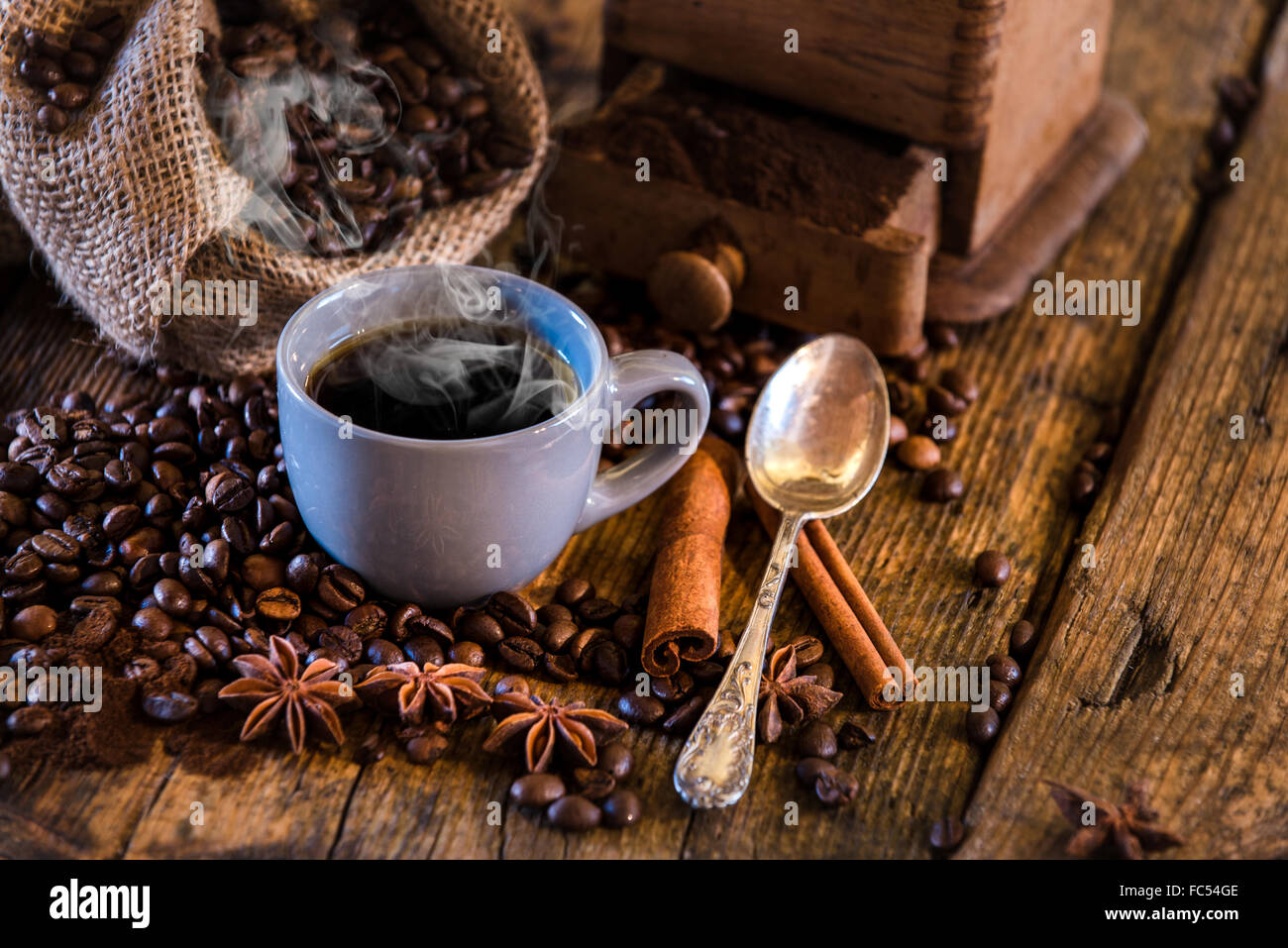 Rural Italian breakfast of coffee and croissant on a wooden table with a kerosene lamp. - Stock Image