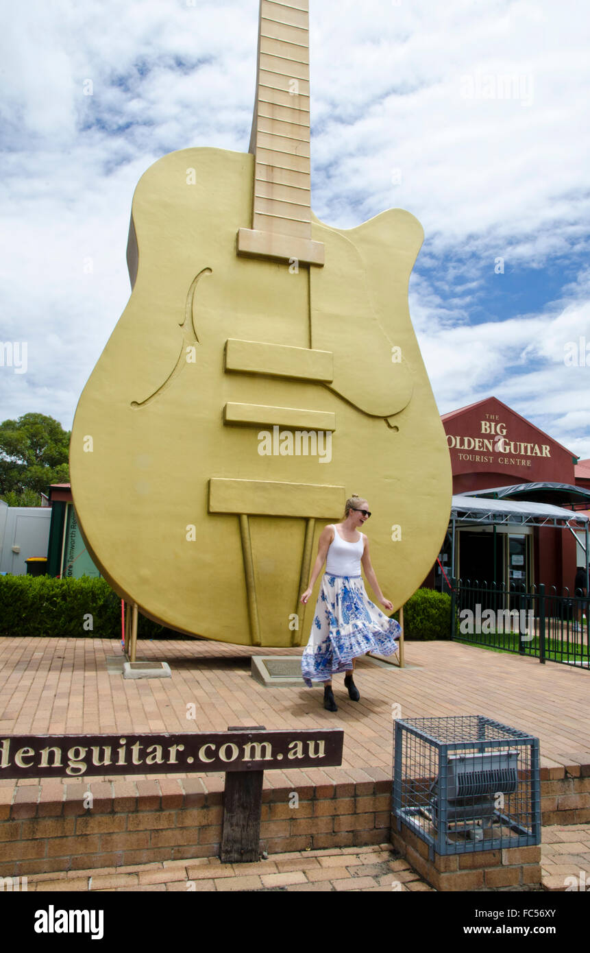 Happy Girl Dancing in front of the Big Guitar at Tamworth NSW Australia - Stock Image
