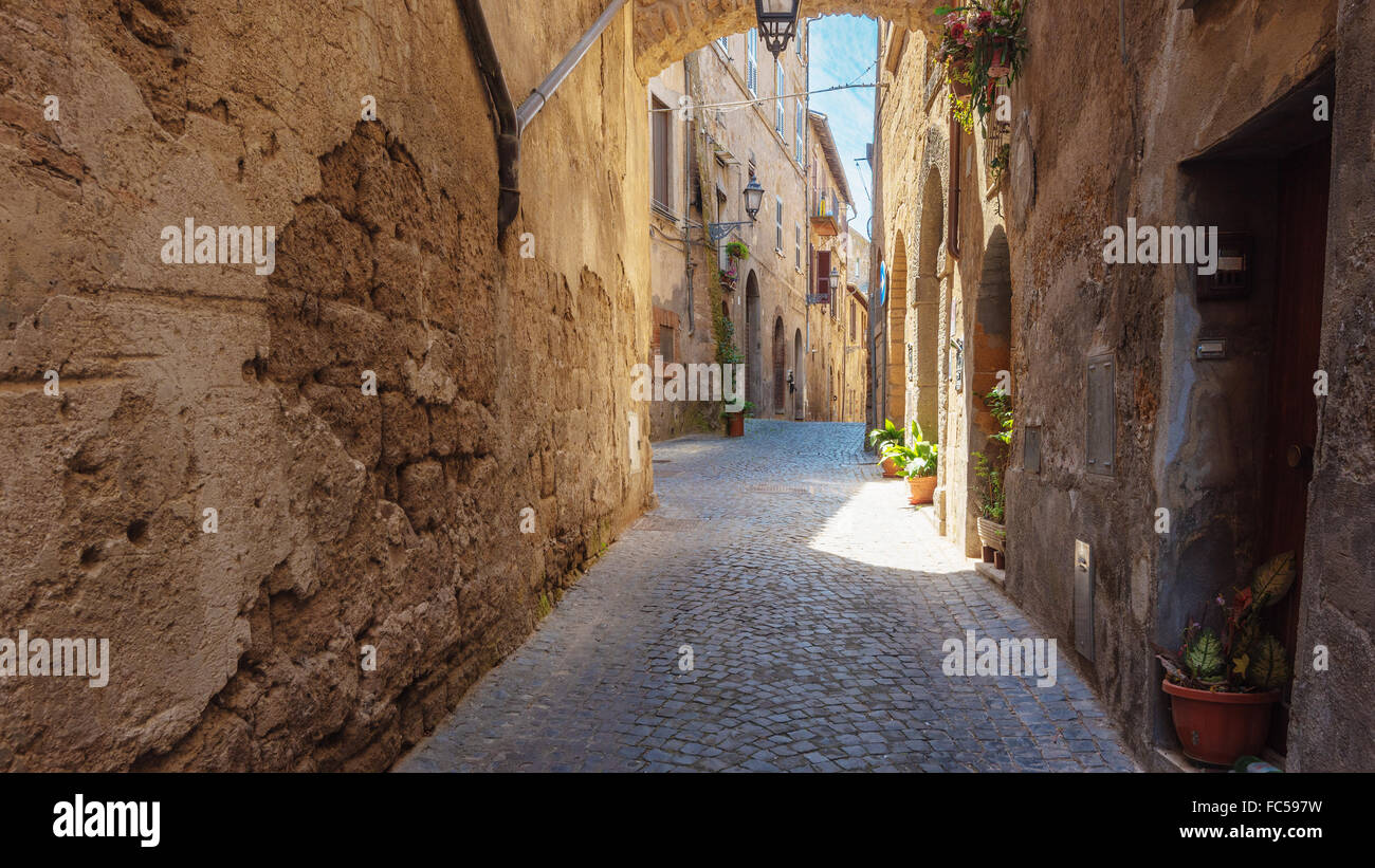 Italian streets with arches on a sunny day and long shadows Stock Photo