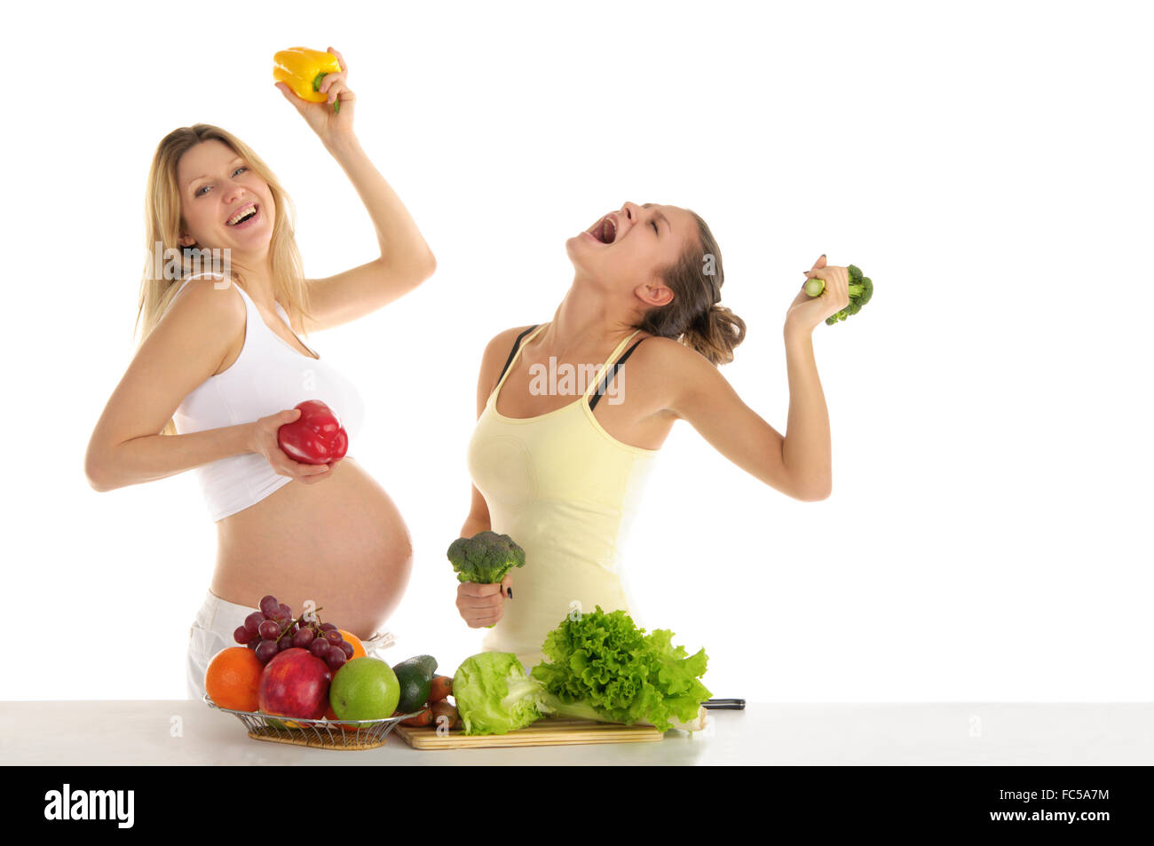 Two women dance with fruits and vegetables - Stock Image