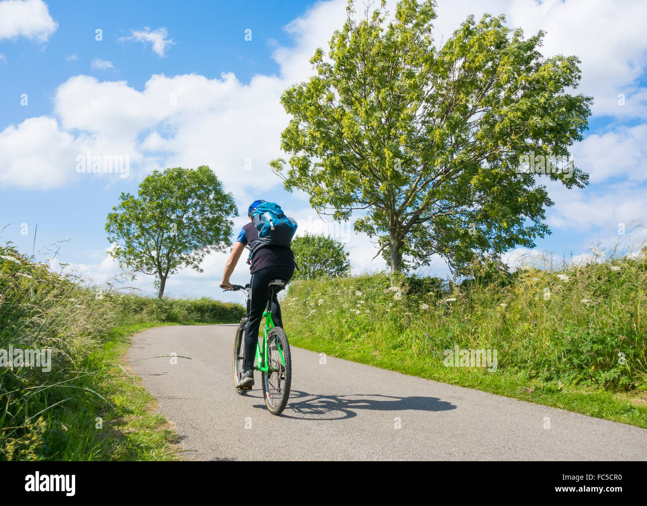 Mountain biker on quiet country lane in Yorkshire Dales National Park, Yorkshire, England, UK - Stock Image
