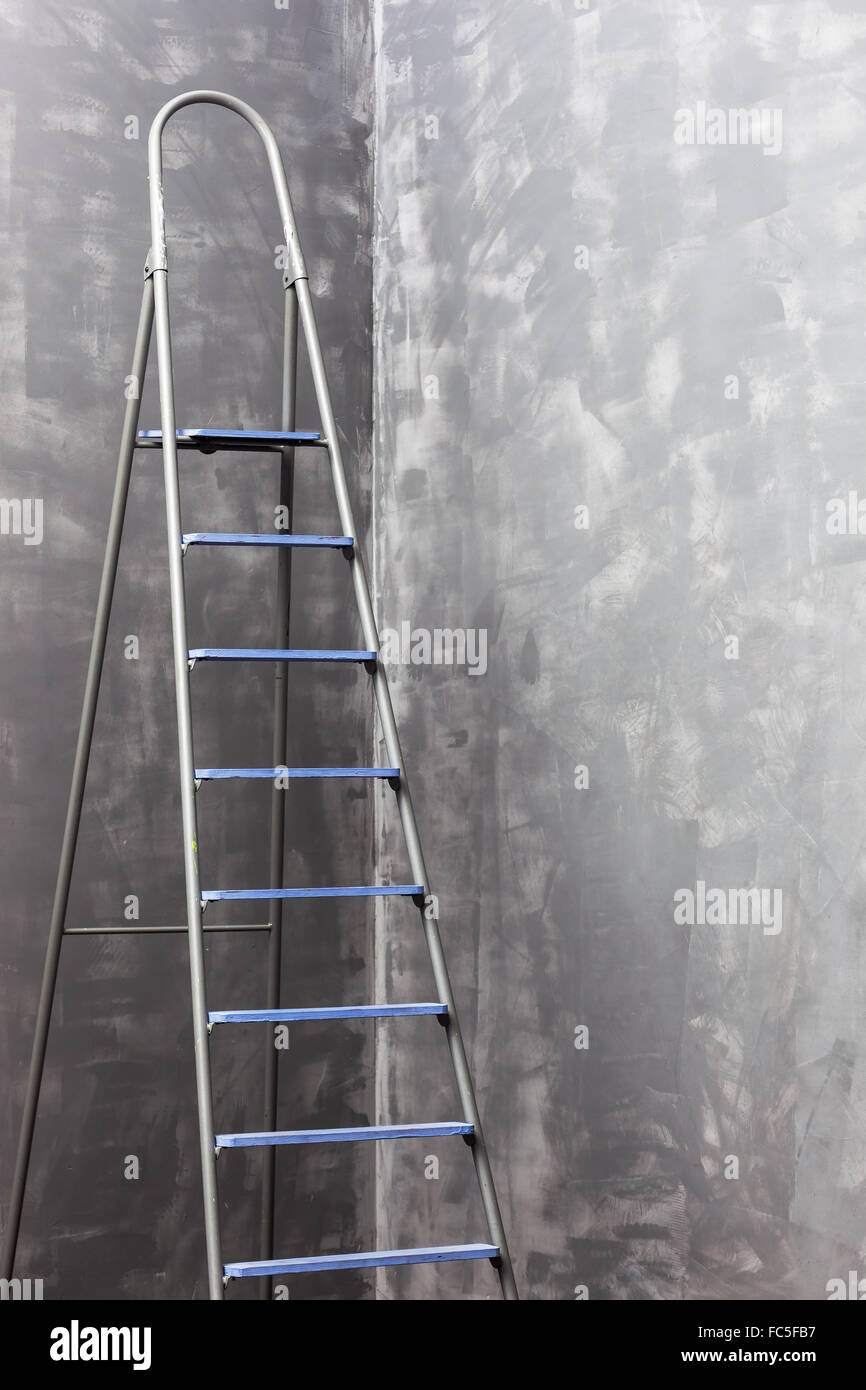 Stepladder standing in the corner near the unpainted walls. Stock Photo