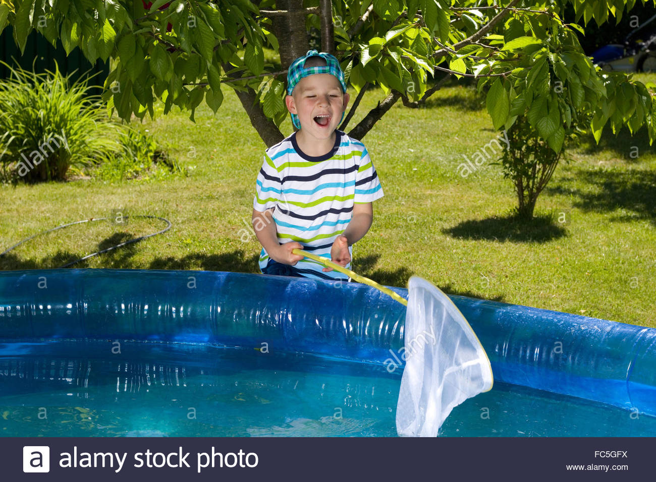 little boy maintains the pool Stock Photo