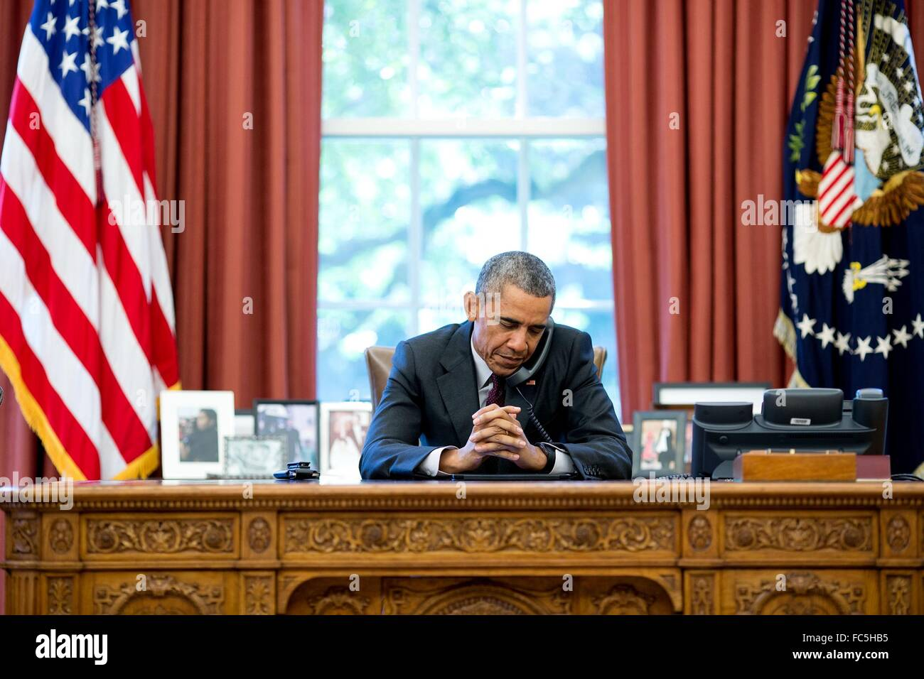 U.S President Barack Obama listens to a prayer during a phone call with pastors on his birthday in the Oval Office - Stock Image