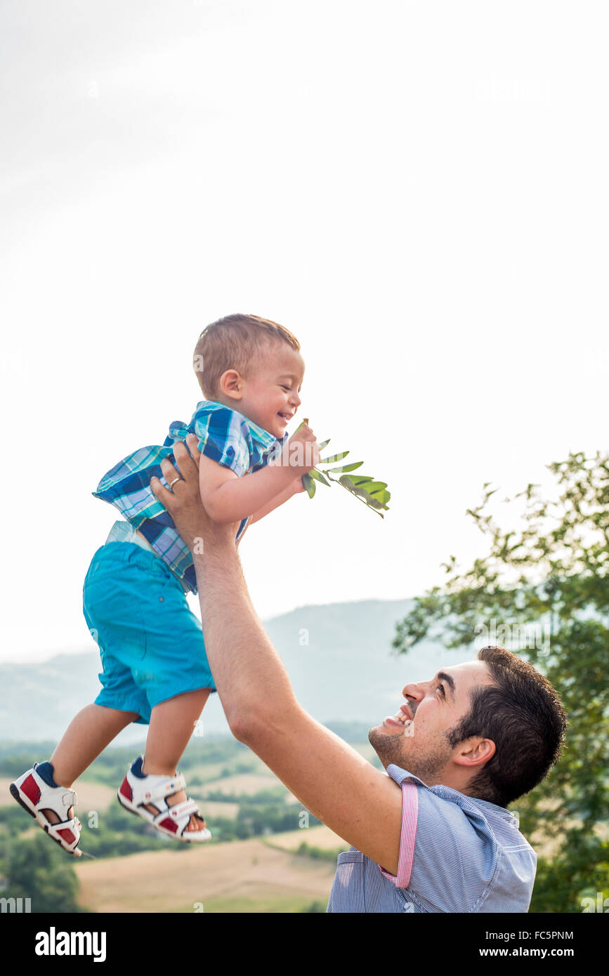 Father Lifting Son in Air - Stock Image