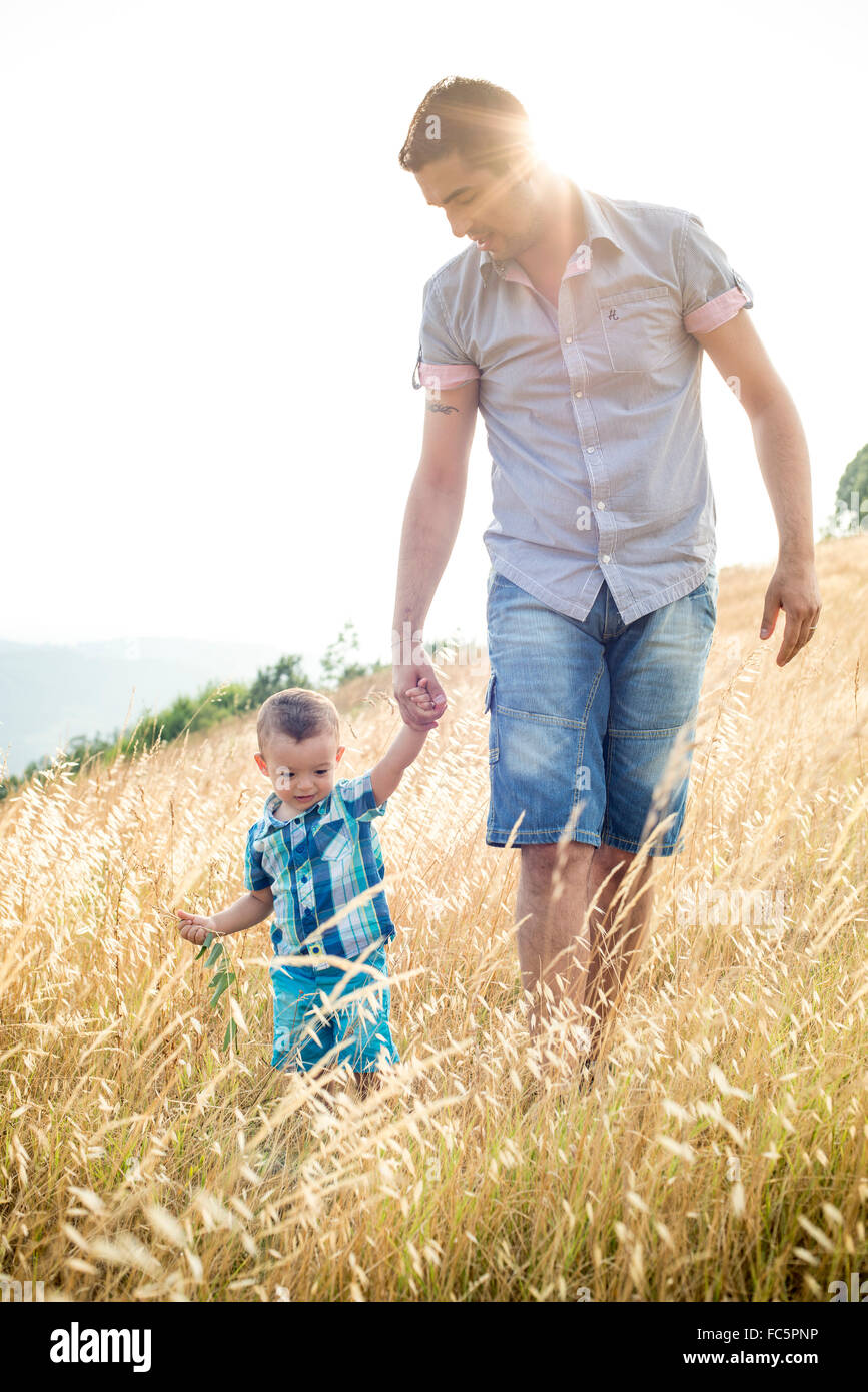 Man and Young Boy Walking Through Field - Stock Image