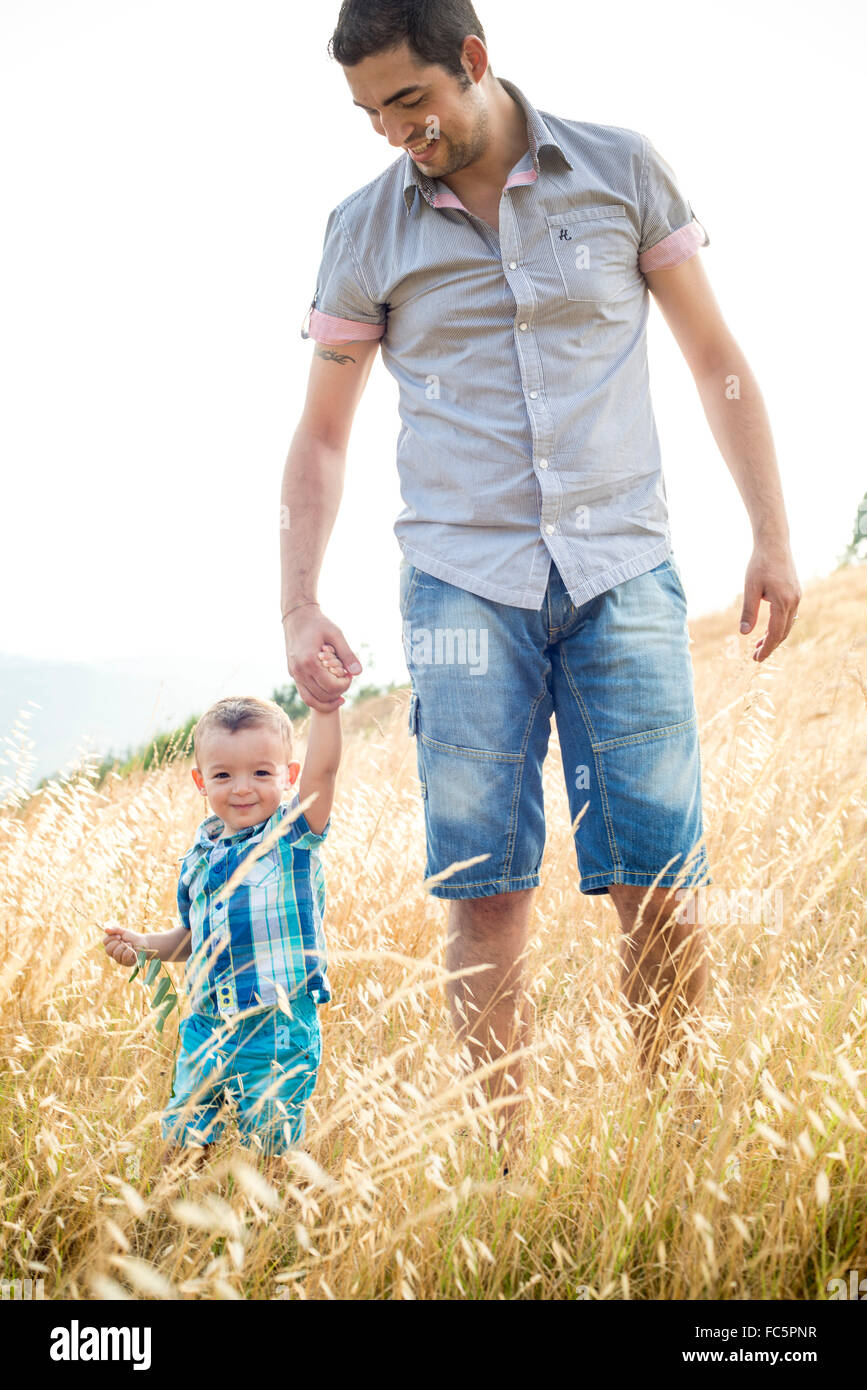 Smiling Man and Young Boy Walking Through Field - Stock Image