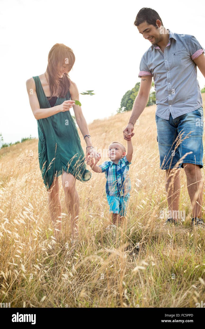 Happy Parents Walking With Young Son in Field - Stock Image