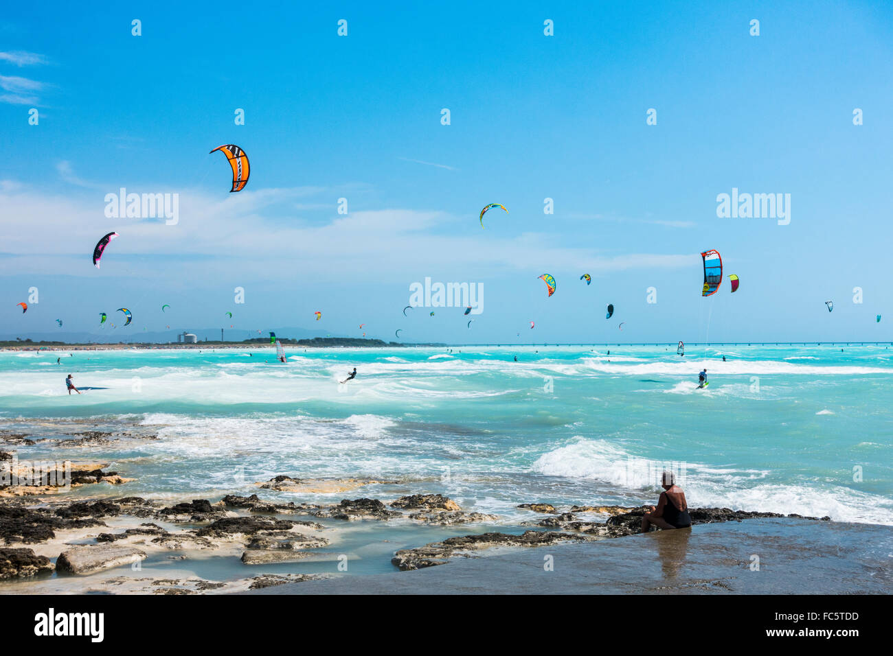 Kitesurfers on the tropical beach in Rosignano Solvay in Tuscany, Italy. The turqoise waters comes from the white - Stock Image