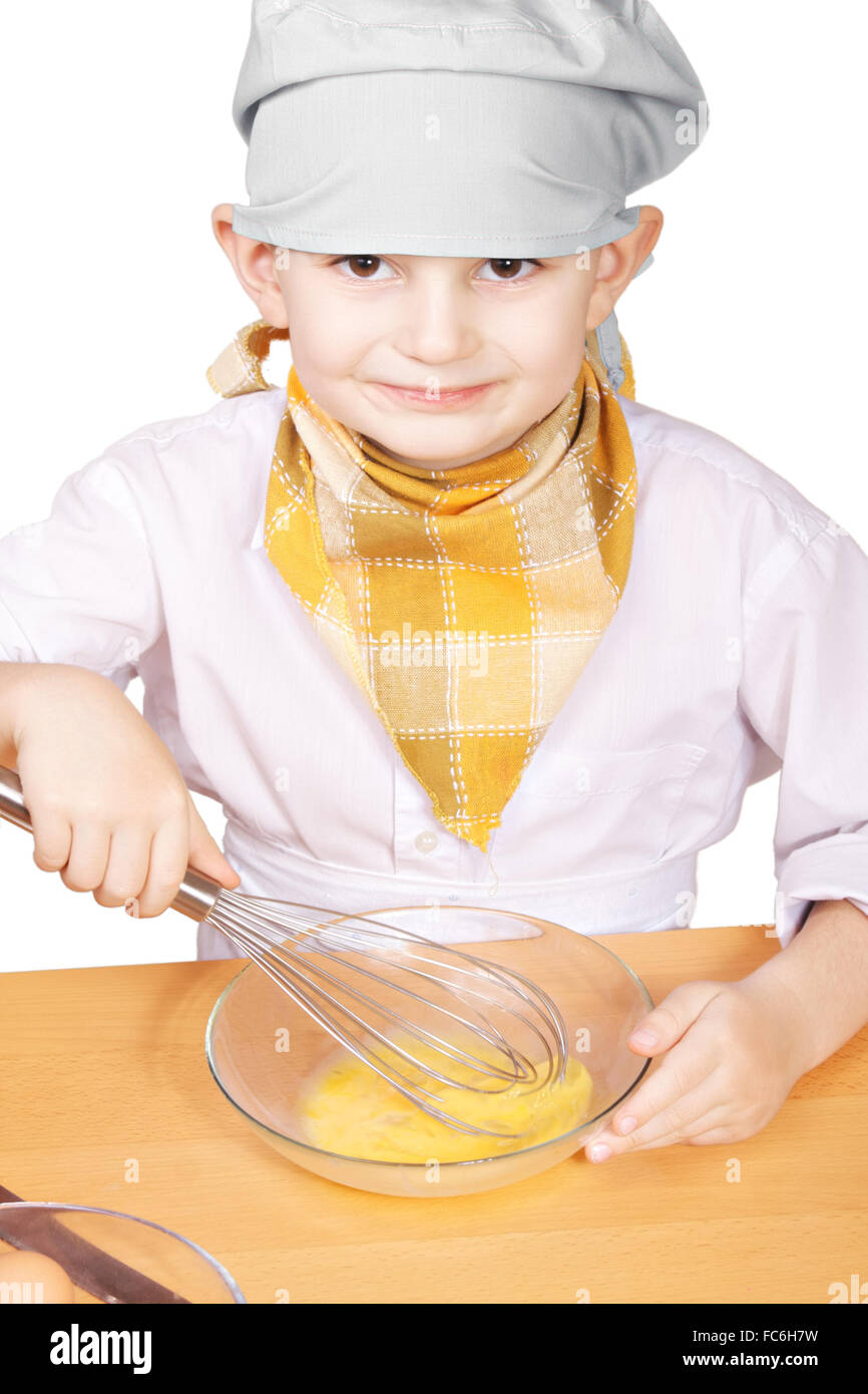 Little smiling cook whisking eggs in a bowl - Stock Image