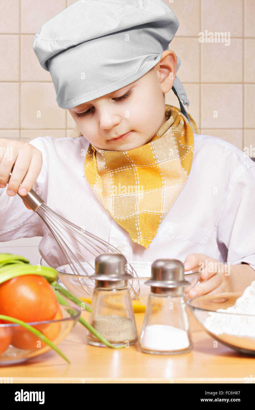 Little cook whisking eggs in a bowl - Stock Image
