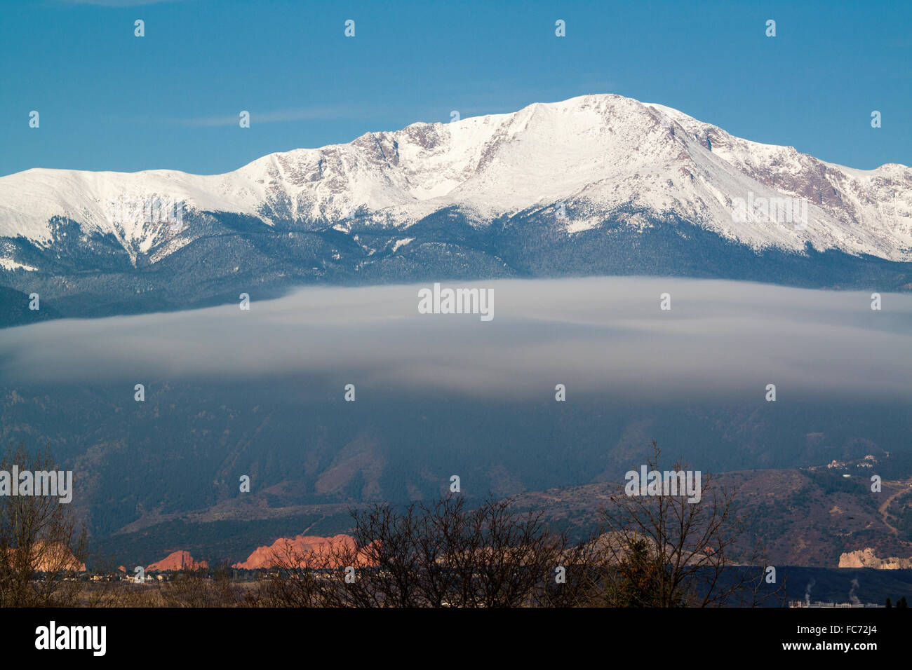 A cloud hangs low in front of snow-capped Pikes Peak on an early spring day - Stock Image