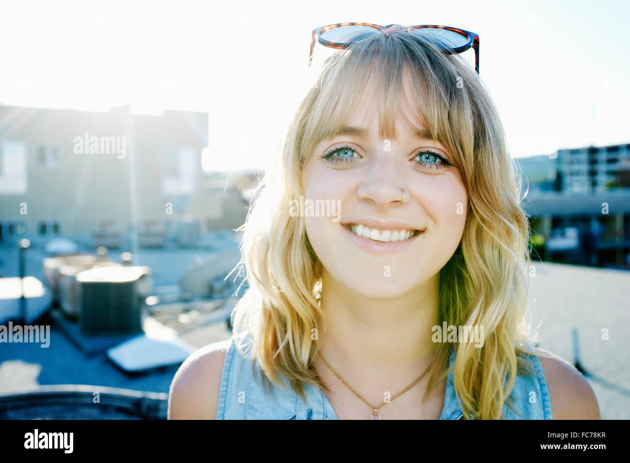 Caucasian woman smiling on urban rooftop Stock Photo