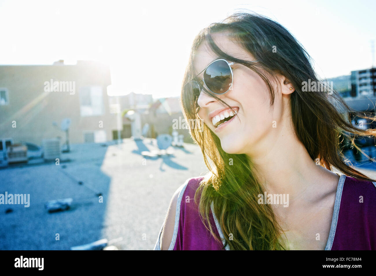 Mixed race woman smiling on urban rooftop Stock Photo