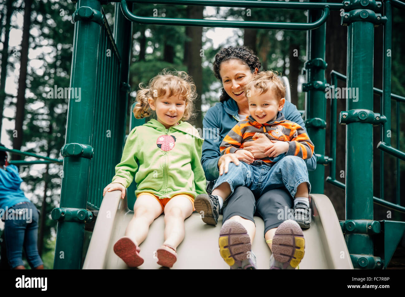 Caucasian mother and children playing on playground Stock Photo