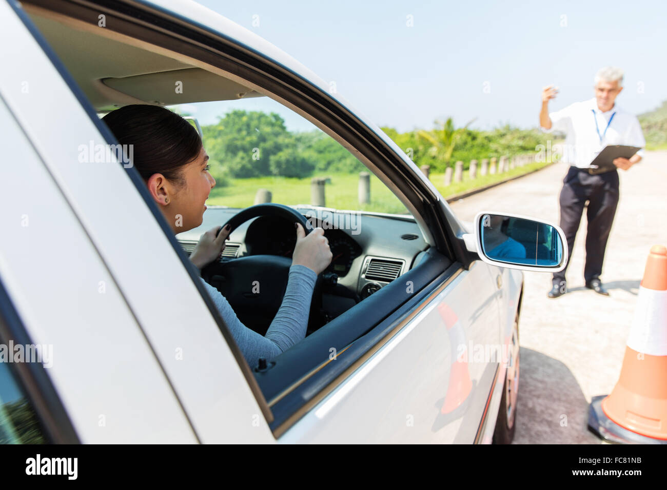 happy young student driver with driving instructor learning to park a car - Stock Image