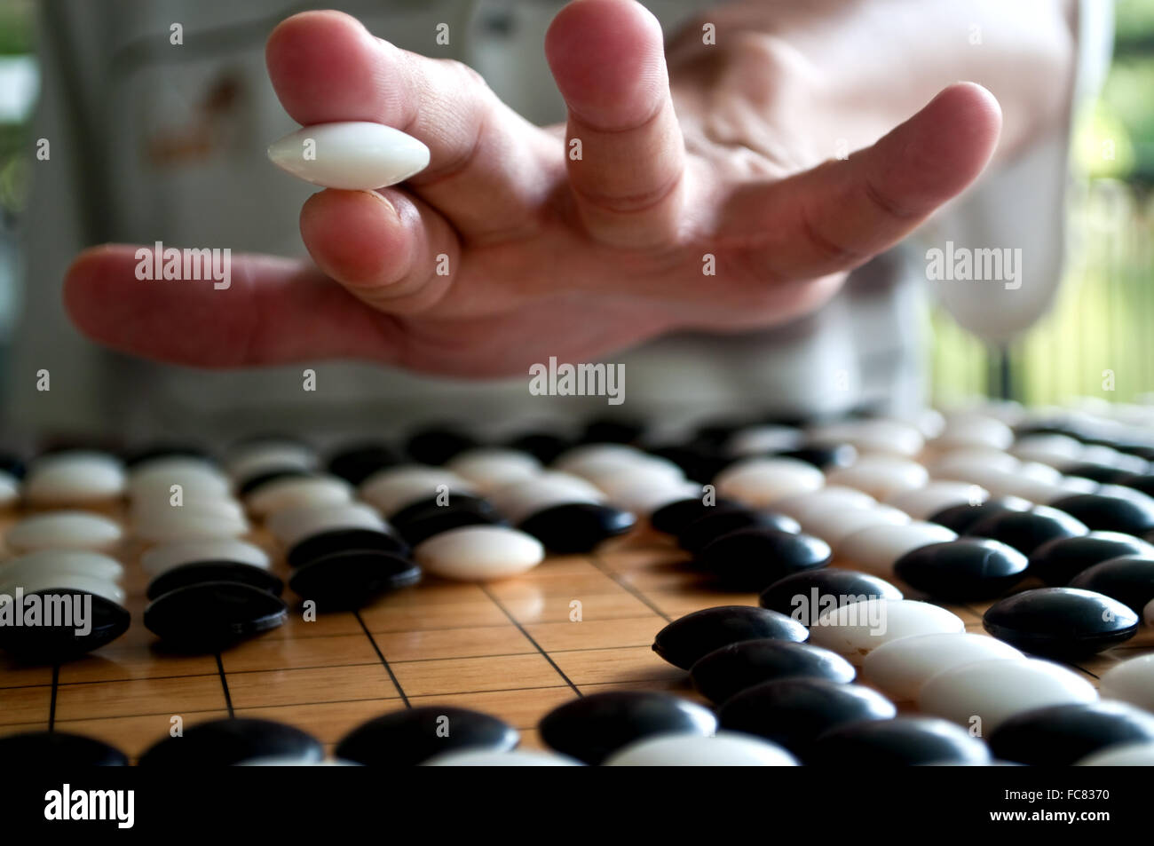 White Go player closeup hand showing how to hold the piece. Selected focus. - Stock Image