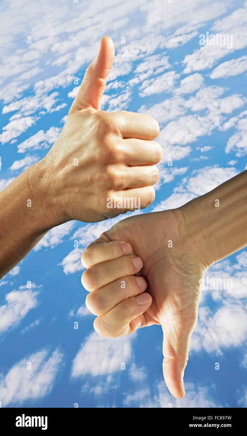 A hand with thumb up and thumb down against cloudy sky. Stock Photo