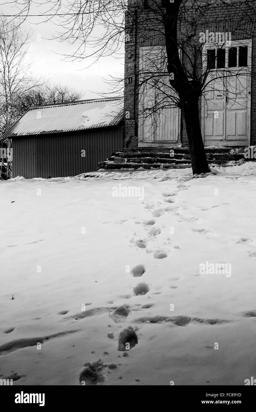 Set of human footprints in the snow lead towards the comfort of a home in a winter setting - Stock Image