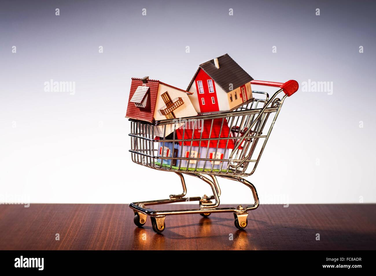 Houses are stacked in a shopping cart. Stock Photo