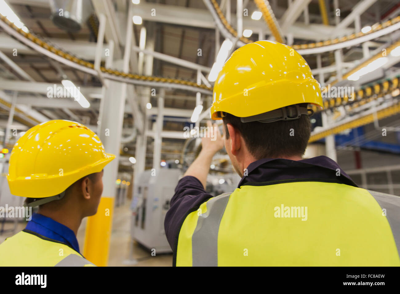 Workers discussing printing press conveyor belts overhead - Stock Image