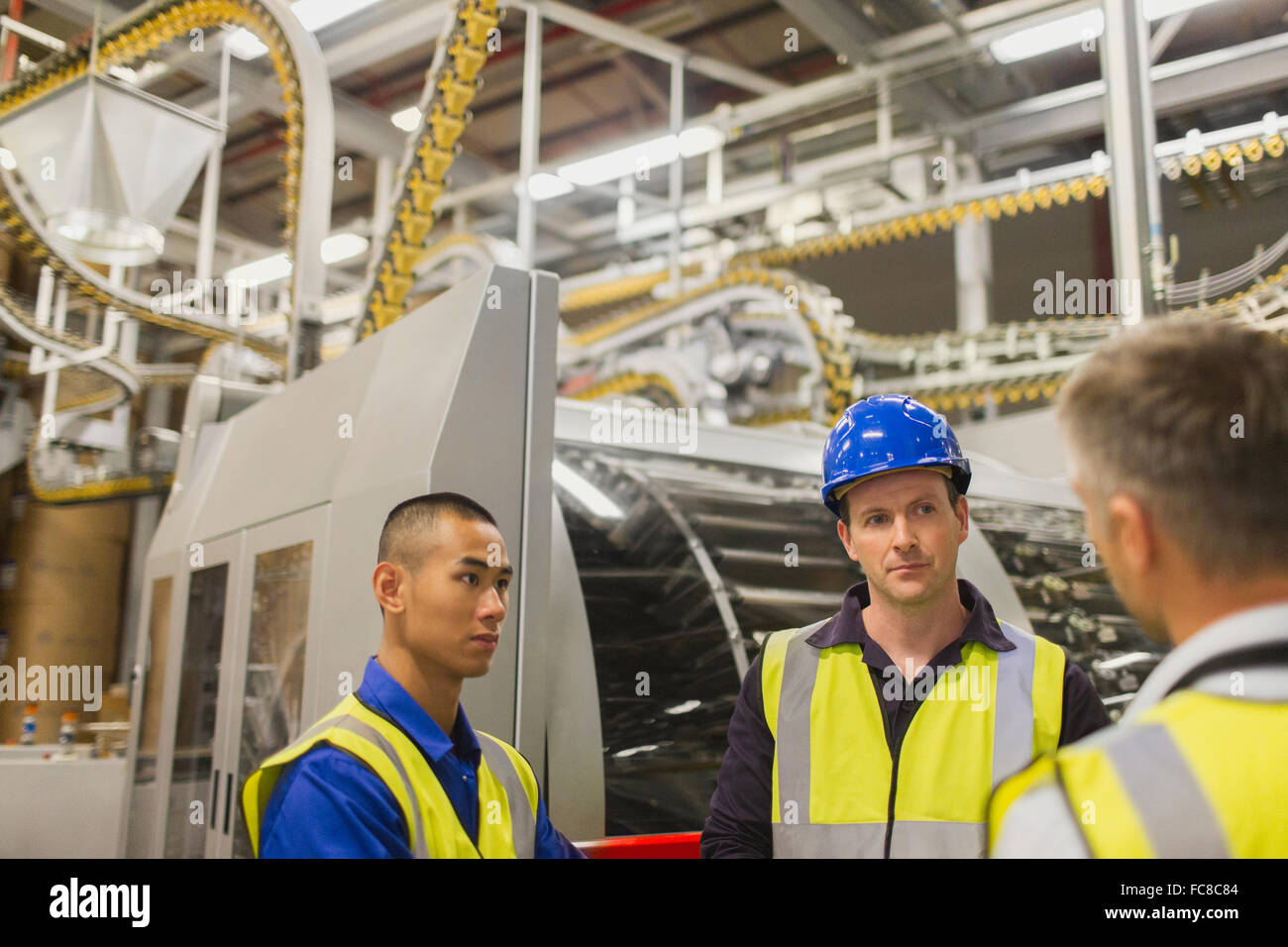 Workers talking in printing plant - Stock Image