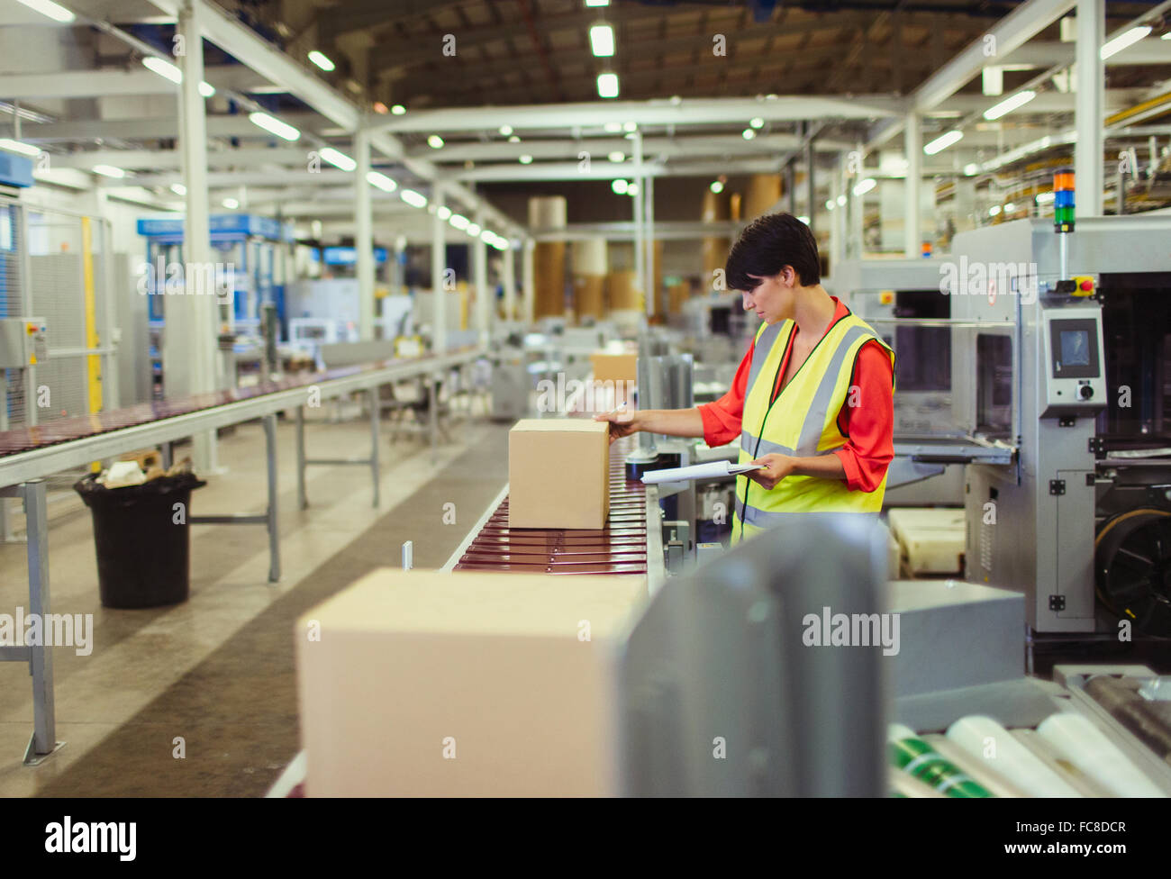 Worker checking cardboard boxes on conveyor belt production line in factory - Stock Image