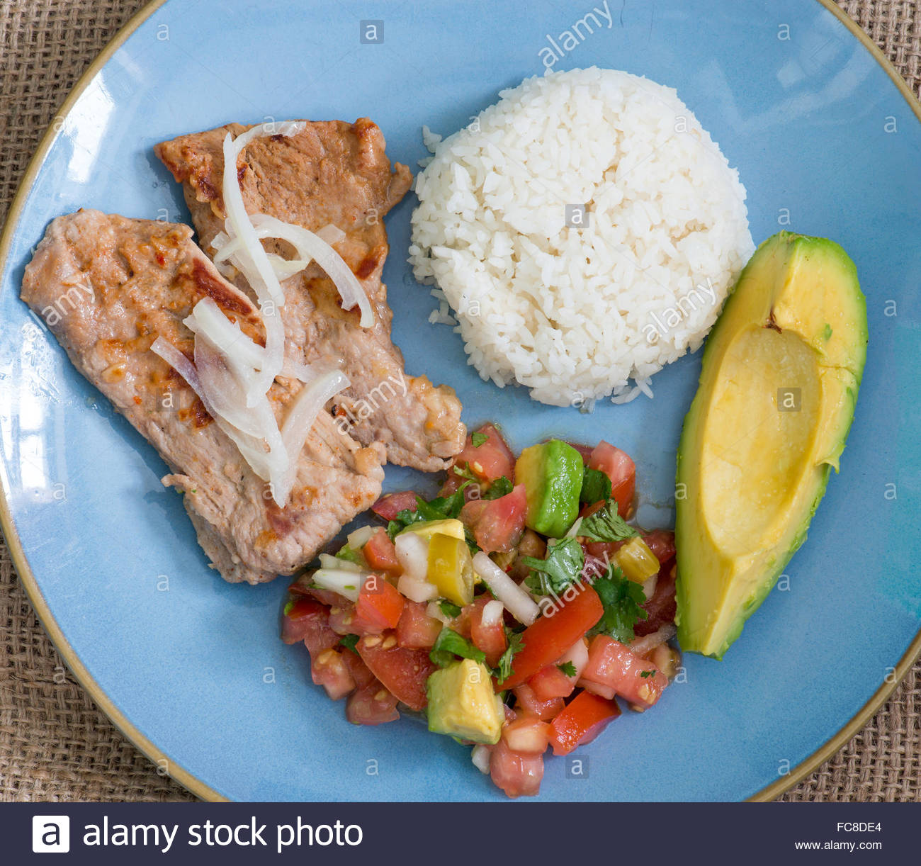 Latin American cuisine fusion: pork steak, white rice,pico de gallo and avocado.Mexican and Cuban cuisine fusion Stock Photo