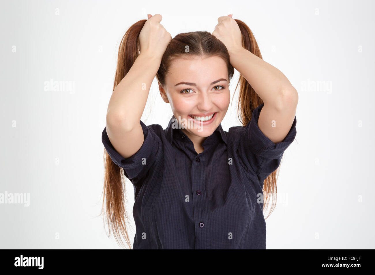 Cheerful beautiful young woman making two ponytails by hands over white background - Stock Image