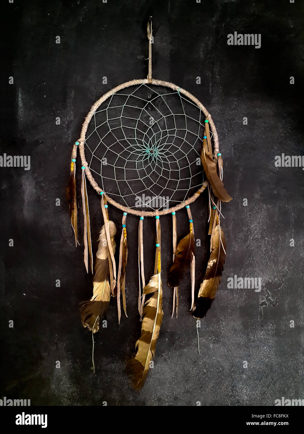 Dreamcatcher hanging on dark grey wall - Stock Image
