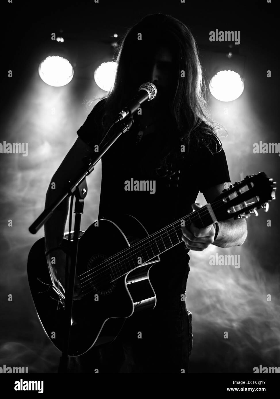 Photo of a backlit young man with long hair in silhouette playing an acoustic guitar on stage. - Stock Image