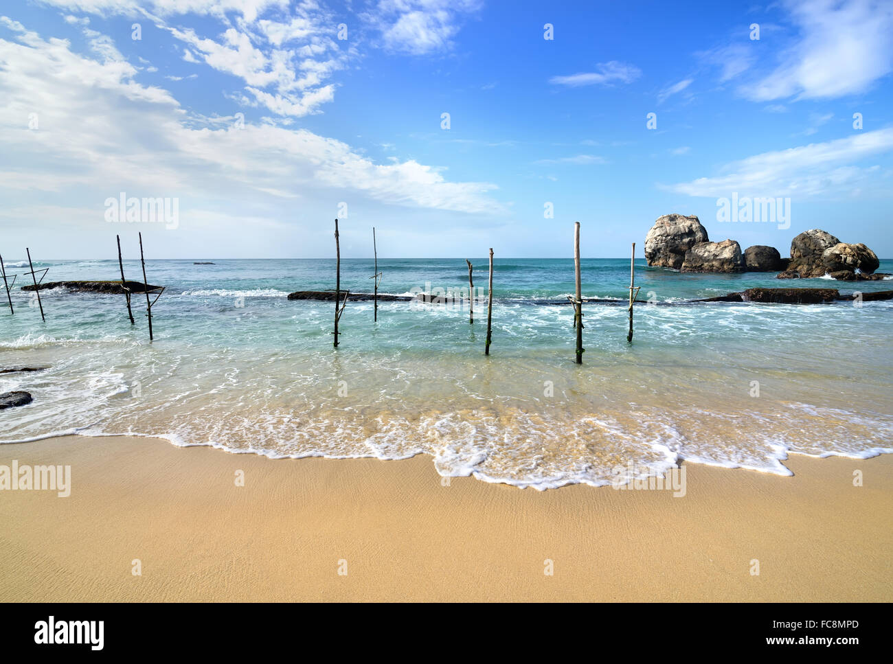 Wooden poles for fishing on a beach of indian ocean in Sri Lanka - Stock Image